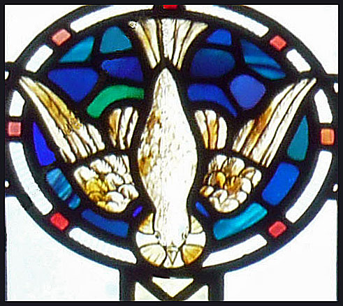 Stained glass light of the Holy Spirit descending as a dove