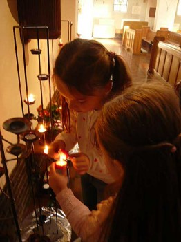 children lighting candles after Mass at St. Edward's Church, Kettering