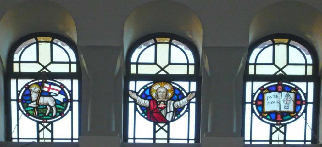 Stained glass window in the clerestory above the north aisle of St. Edward's Church, Kettering. It depicts Christ, a lamb and flag, and an open book