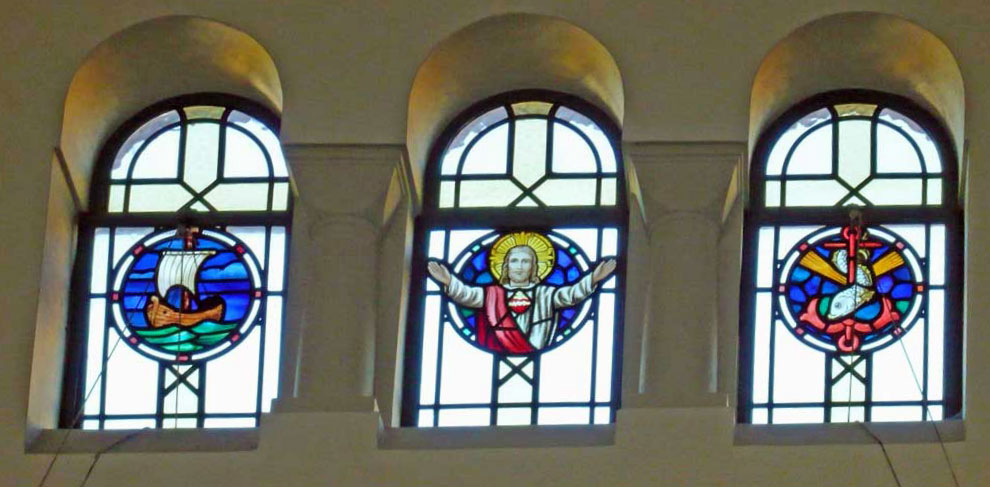Stained glass window in the clerestory above the north aisle of St. Edward's church, Kettering, depicting Jesus, a ship and a fish wrapped around an anchor