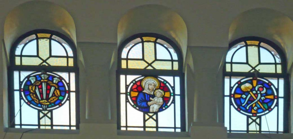 Stained glass window in the clerestory above the north aisle in St. Edward's church, Kettering, depicting Mary holding baby Jesus, three nails piercing a crown of thorns, hammer and pincers in the form of a cross