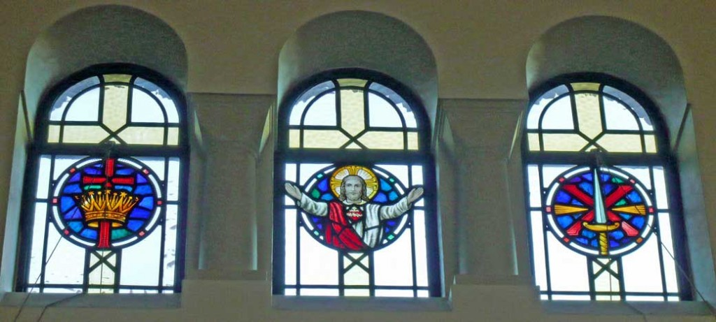Stained glass window in the clerestory of the South aisle depicting Jesus, an empty cross encircled by a crown, a sword atop a cross