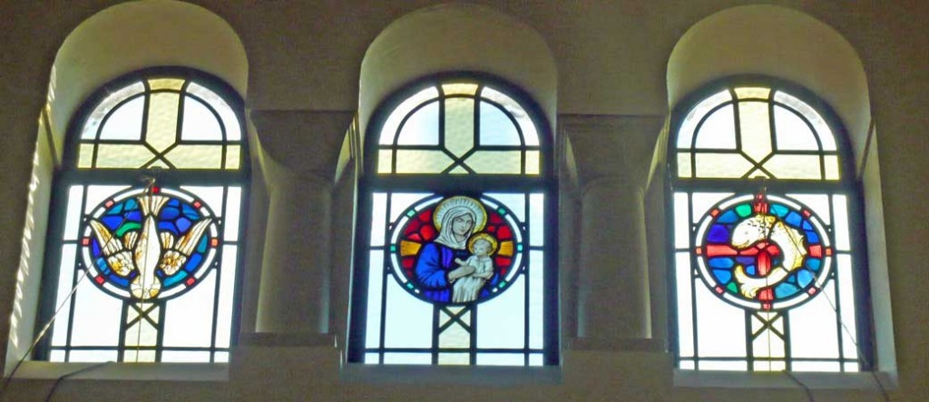 triple light stained glass window in the clerestory of the South aisle depicting Madonna and child, dove descending, fish atop an empty cross