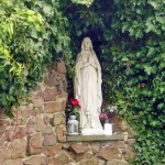 Statue of Our Lady of Lourdes in the grotto outside of St. Bernadette's church, Rothwell