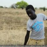Fabiano walking home with water for his mother in Uganda
