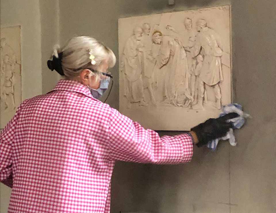 Woman cleaning Station of the Cross during St. Edward's Church redecoration June 2020