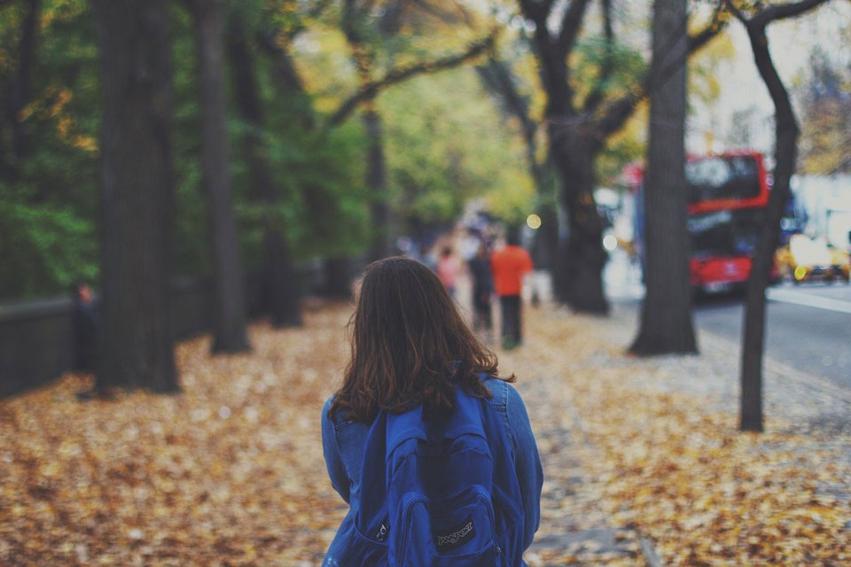 Young girl with a backpack walking along an autumnal street to school