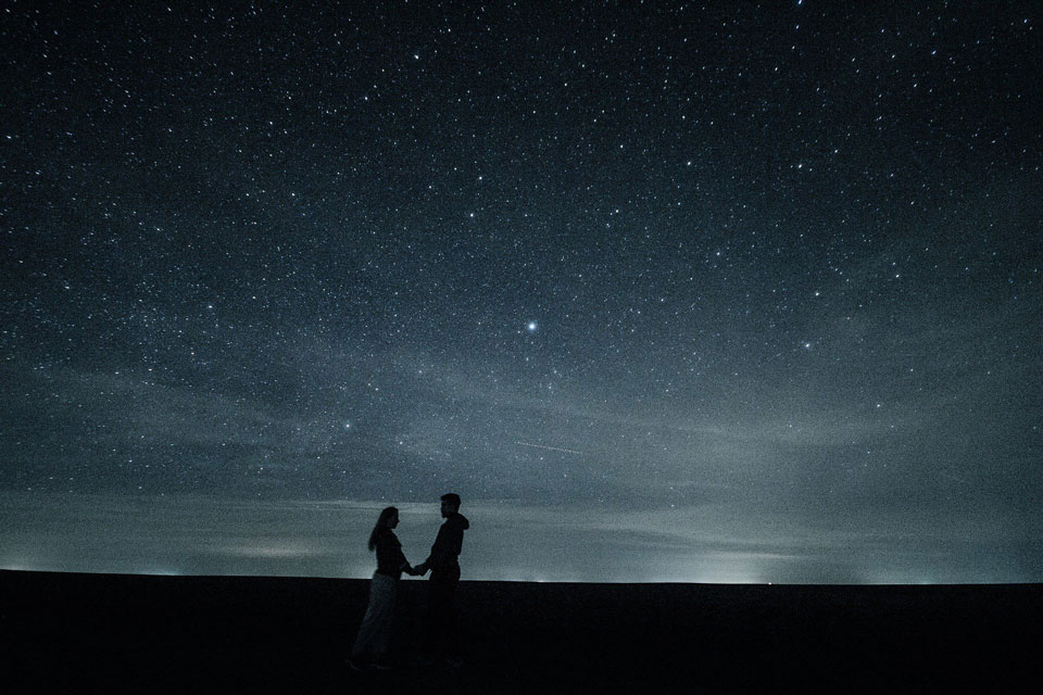 Couple holding hands under a starry sky