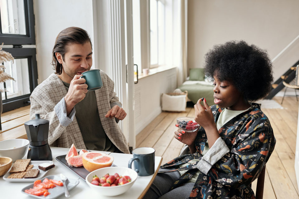 Couple sitting eating fruit at a breakfast table