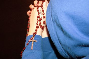 Child wearing a hoodie praying the rosary