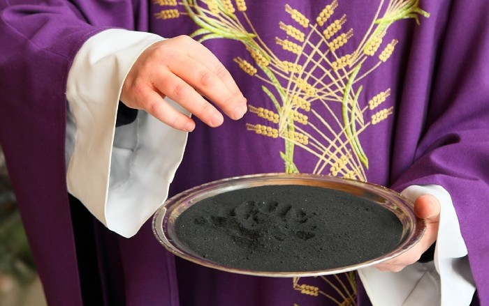 Priest holding a plate with ashes on it for Ash Wednesday service