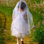 back view of a young girl in first holy communion dress and veil in a meadow