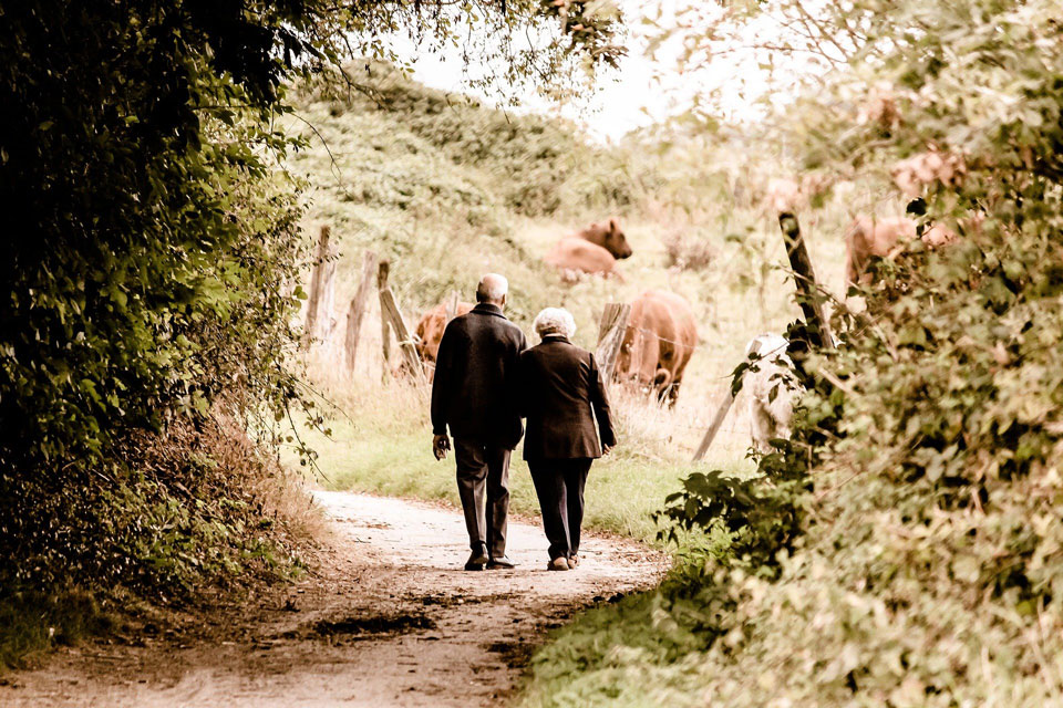 An old couple walking close together on a leafy track