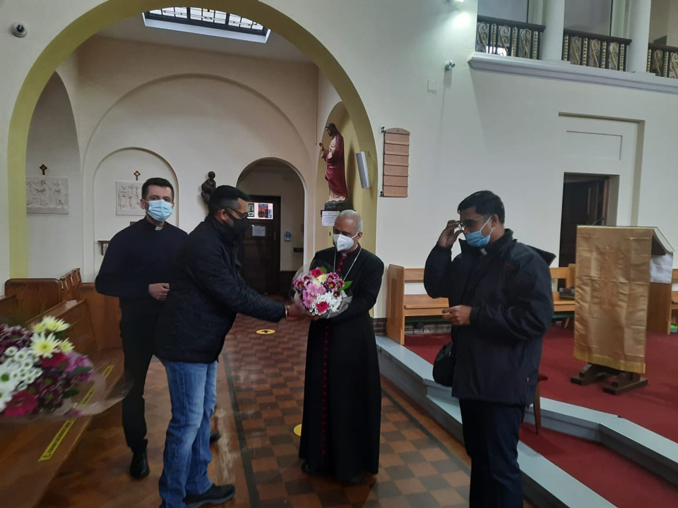 Flowers being given to Bishop Joseph inside St. Edward's Church, April 2021