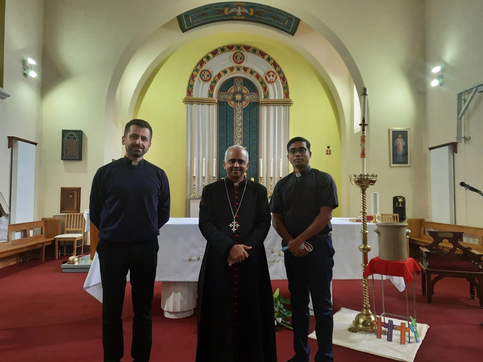 Fr Gregory, Bishop Joseph, Fr Ebin standing in front of the altar in St. Edward's Church, April 2021