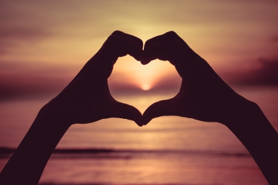 Silhouette of hands held together to form a heart against a setting sun background